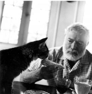 Hemingway feeding his cat